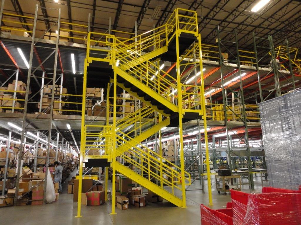 woman behind OSHA yellow steel stairway with dark hair and gray jumpsuit working with boxes in e-commerce shipping facility