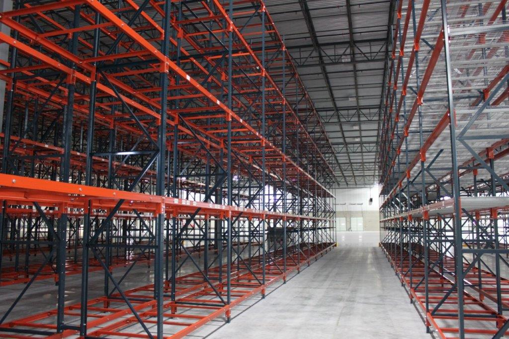 red structural steel selective racks utilizing high ceilings in shipping warehouse card