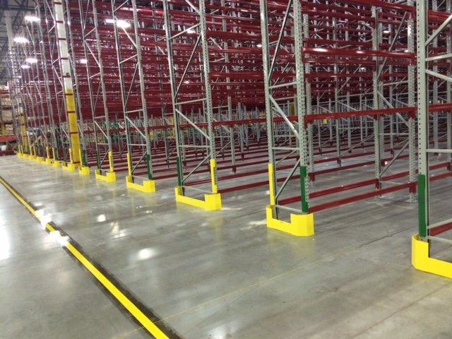 OSHA yellow rack guards and post protectors on ends of rows of red stainless steel racking in shipping warehouse